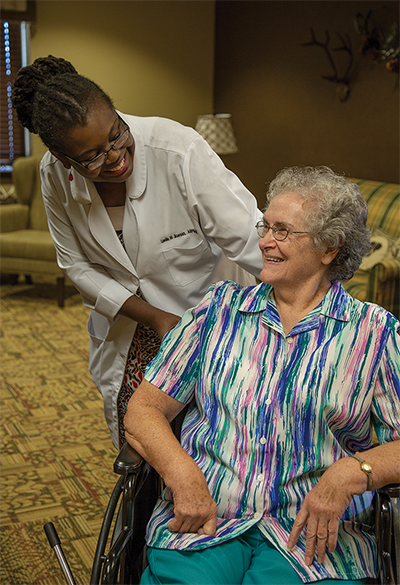 GA MedGroup nurse smiling at patient in wheelchair